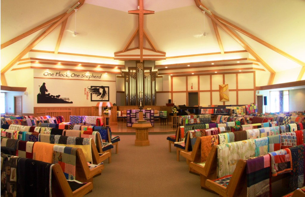 Piecemakers' quilts line the sanctuary pews before being sent on Global Mission